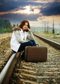 A woman waiting on a train.